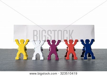 Colorful Diverse Miniature People Figurines Standing In A Row On A Dark Stone Slate Plate. Blank Ban