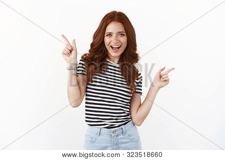 Cheeky Playful Redhead Girl Dancing Upbeat, Pointing Sideways, Showing Left Right Copy Space Promos,
