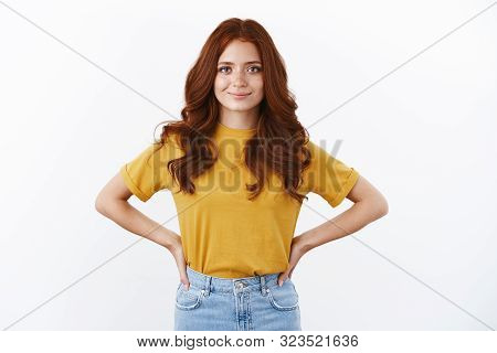 Ambitious And Confident Cute Hipster Girl With Red Curly Hair In Yellow T-shirt Hold Hands On Waist