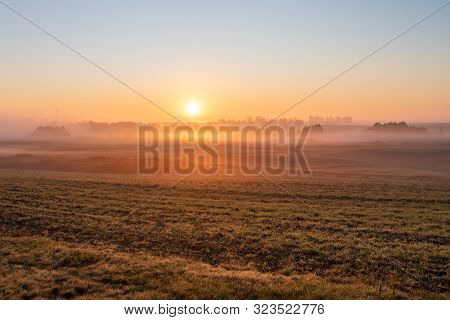 Fog On Misty Fields At Sunrise. The Rising Sun Over The Fields In Central Europe.