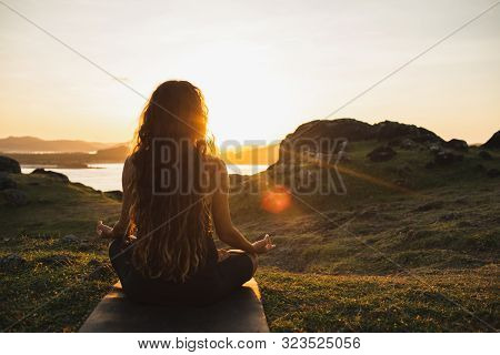 Woman Meditating Yoga Alone At Sunrise Mountains. View From Behind. Travel Lifestyle Spiritual Relax