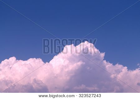 Pink and gray puffy cumulus clouds in the bright blue sky poster