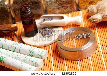 Akupunkturnadeln, Moxa-Sticks, Lavendel-Blütenblätter mit kaltgepressten Öl, Giner und Kräuter in Gläsern. TCM-T