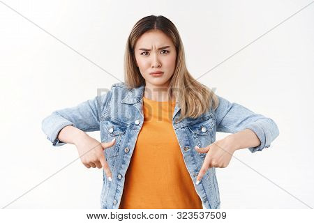 What suppose mean. Frustrated puzzled young concerned blond asian girl frowning perplexed pointing down squinting intense suspicious not believe add standing upset white background poster