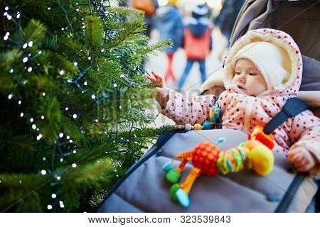 Adorable Baby Girl Sitting In Pushchair Near Christmas Tree Decorated With Light Garland