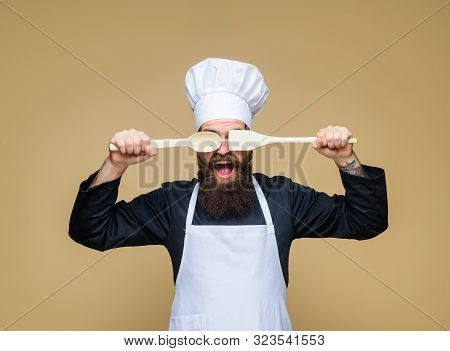 Bearded Man Preparing To Cook Food. Bearded Cook With Wooden Spoon And Spatula In Hand. Handsome Che
