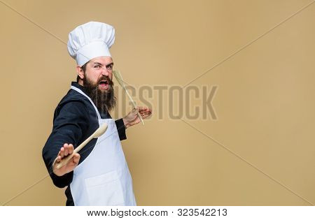 Handsome Chef Cook With Kitchen Utensils. Chief Man In Cook Uniform Holds Wooden Kitchen Cooking Too