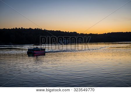 A Pontoon Boat With Lights Just Aver Sunset On White Lake In Sullivan County New York.
