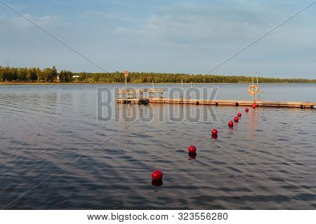 The Pier And The Red Buoys At A Beach In The Rural Finland. You Can Still Feel The Summer On This Au