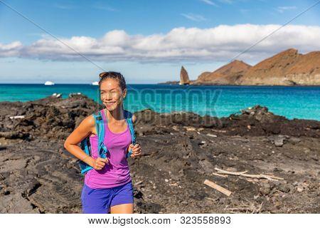 Galapagos tourist walking on Santiago Island in Galapagos Islands. Pinnacle Rock and Bartolome Island in background. Famous Galapagos cruise ship destination.