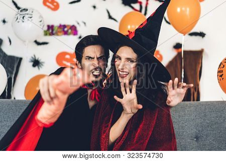 Couple Having Fun Wearing Dressed Carnival Halloween Costumes And Makeup Posing With Bats And Balloo