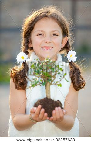 girl holding tree as environmental or nature concept ( focus on child )
