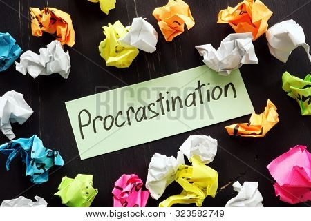 Procrastination Sign And Colored Paper Balls On Table.