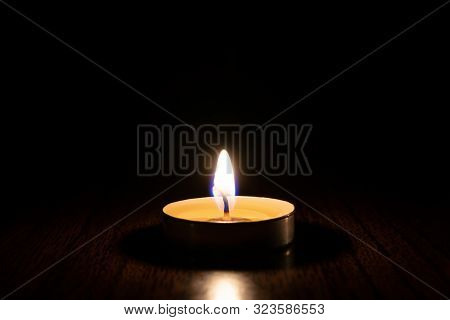 Burning Candle In The Center Of The Frame On A Black Background. The Concept Of Mourning, Grief Or S