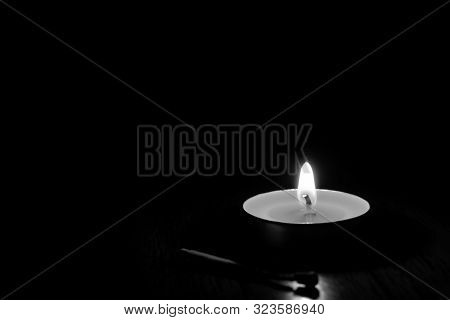 Candle Burning In The Black Background.
