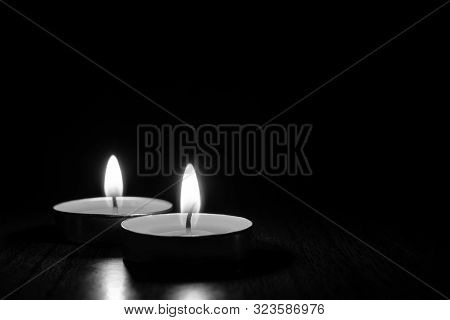Candles Burning In The Black Background. Black And White Photo.