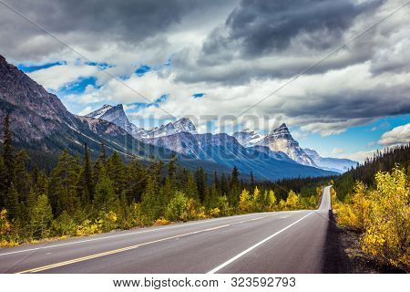 The highway crosses the Rocky Mountains of Canada. Magnificent northern autumn. Canadian Rockies. The concept of active, automotive, environmental and photo tourism