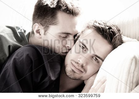 Attractive Gay Man With Goatee Looks At Camera As His Partner Or Husband Kisses His Cheek