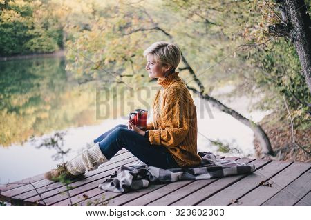 Beautiful Woman Blond With Short Haircut And Blue Eyes Sitting Near Lake With Cup Of Hot Tea. Cozy F