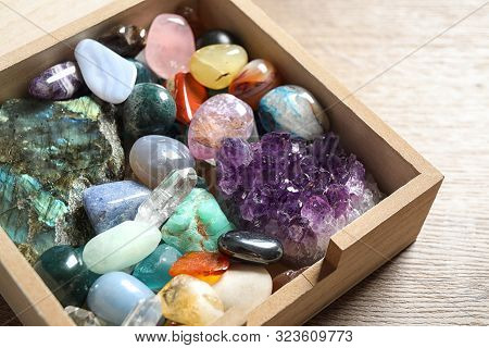 Box With Different Beautiful Gemstones On Wooden Table