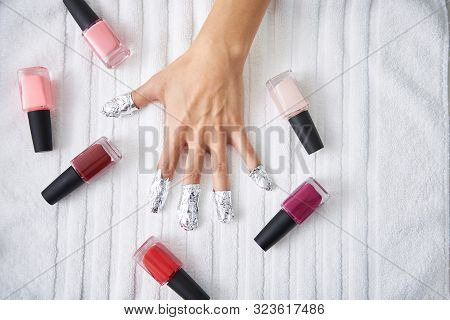 Female Hand With Strips Of Foil On Fingers And Nail Polishes On Towel