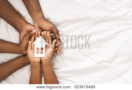 Adoption And Family Housing Concept. Cutout Paper House In Hands Of African American Family Over Whi