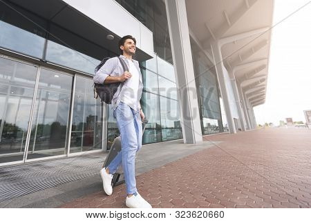 Homecoming. Happy Millennial Man Walking With Luggage Out Of Airport Building, Free Space