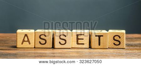 Wooden Blocks With The Word Assets. Resource Owned By The Business. Financial Accounting. Money And