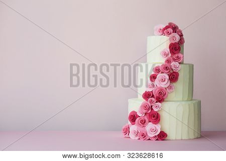 Tiered wedding cake with sugarpaste roses in pink