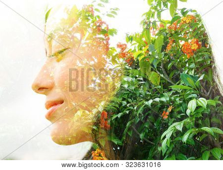 Double exposure profile portrait of a young, relaxed natural beauty with closed eyes and a smile combined with bright green leaves and flowers on an isolated white background