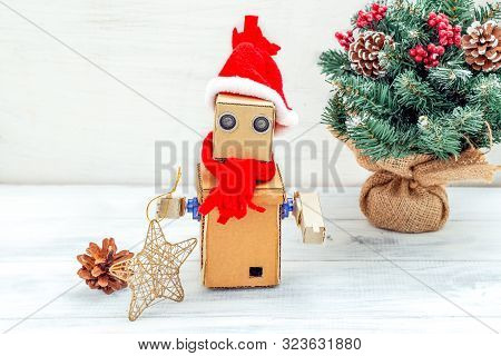 Cardboard Robot With Hands In Santa Hat On A White Wooden Background And Christmas Tree. Christmas C