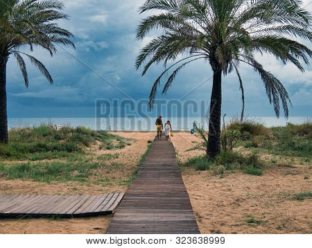 Elderly Couple Walking On A Wooden Walkway On The Beach Of Gandia, Valencia, On A Rainy And Cloudy D
