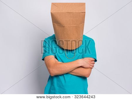 Portrait of offended teen boy with paper bag over head with crossed arms. Unhappy sad child pulling paper shopping bag over head, isolated on white background. Teenager folded hands in bad mood.