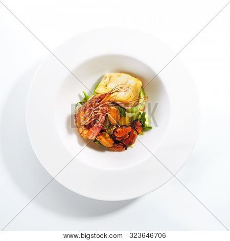 Exquisite serving warm seafood salad with avocado on white restaurant plate isolated. High cuisine restaurent sea food salat with grilled shrimp, mussels and squid in modern minimalist style topview