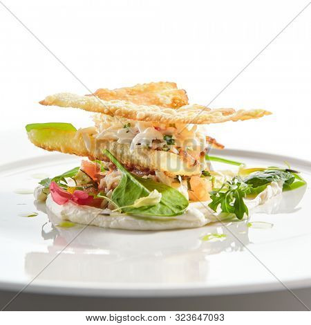 Crab napoleon with pike caviar sauce closeup. Natural seafood restaurant menu item. Delicious snack, exquisite dish isolated on white background. Tasty fresh shellfish meat snack closeup