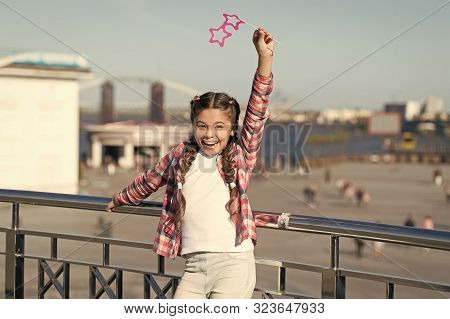 Absolutely thrilled. Happy party girl on urban background. Adorable girl holding prop glasses for party fun. Cute small child smiling with star shaped party goggles. Taking pleasure in a party. poster