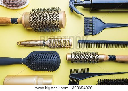 Various hair dresser and cut tools on yellow background with copy space poster