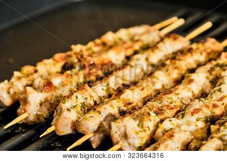 Cooking Homemade Tasty Pork Meat Souvlaki Spiced With Oregano On Grill, Traditional Greek Food