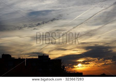 Urban Silhouette With Colorful Sky Covered In Contrails And Clouds During Sunrise.