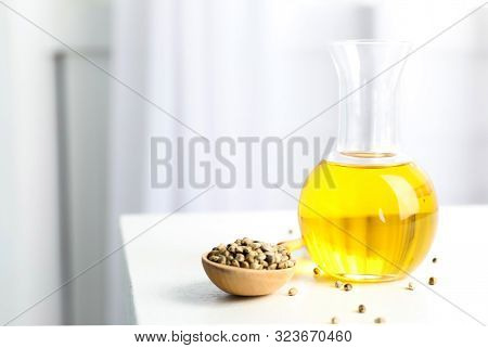 Bottle With Hemp Oil And Seeds On White Table Indoors. Space For Text