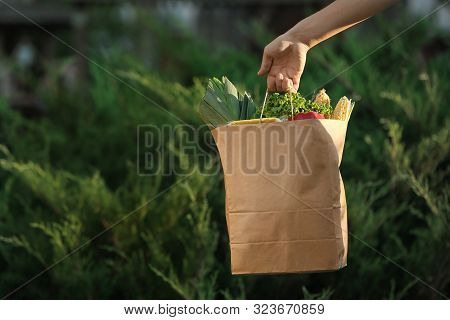Woman Holding Paper Bag With Fresh Vegetables Outdoors, Space For Text