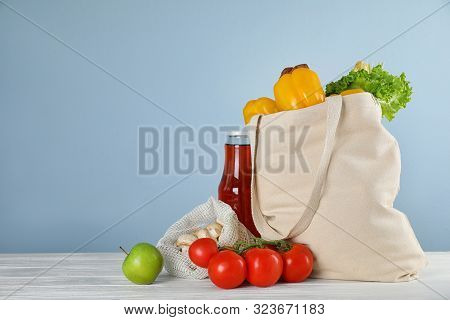 Shopping Bag With Fresh Vegetables And Other Products On White Wooden Table Against Light Blue Backg