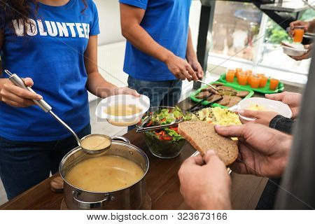 Volunteers Serving Food To Poor People In Charity Centre, Closeup