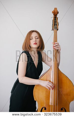 Beautiful Young Woman Musician Playing On A Vintage Double Bass On A Black Background In A Studio.