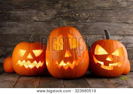 Halloween pumpkins head jack o lantern with candle inside on wooden background