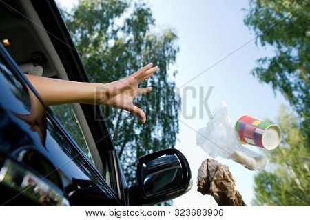A Female Hand Throws A Handful Of Garbage Accumulated In The Car Through The Open Window Of The Car