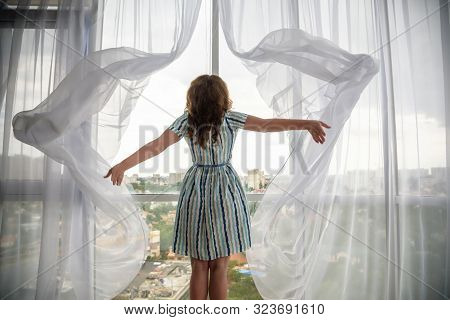 Rear View Of A Young Joyful Woman Wearing Fashion Dress And Holding The Curtains Open To Look Out Of