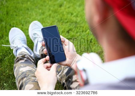 Focus On Stylish Sensory Smartphone In Male Hands. Guy In Casual Clothes Sitting On Green Grass And