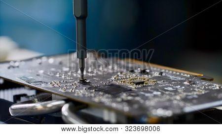 Pc Technician Screws Chipset Of Graphics Card To Ventilator Installing It.