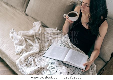 High Angle View Of Dreamy Young Adult Woman Enjoying Cup Of Tea, Holding Paper Book In Hand, Sitting